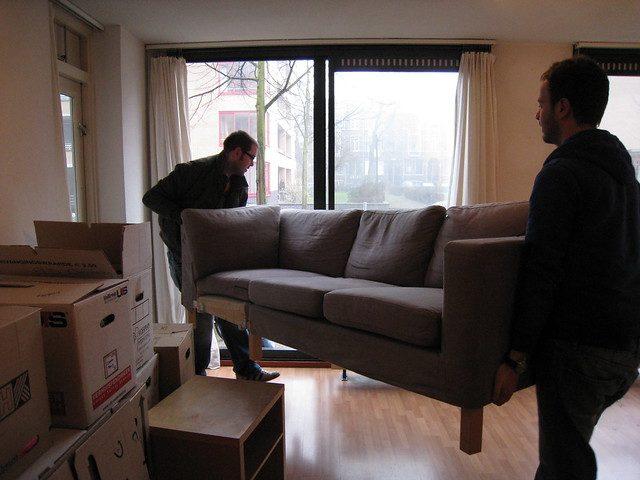 Twee jongens verhuizen een bankstel