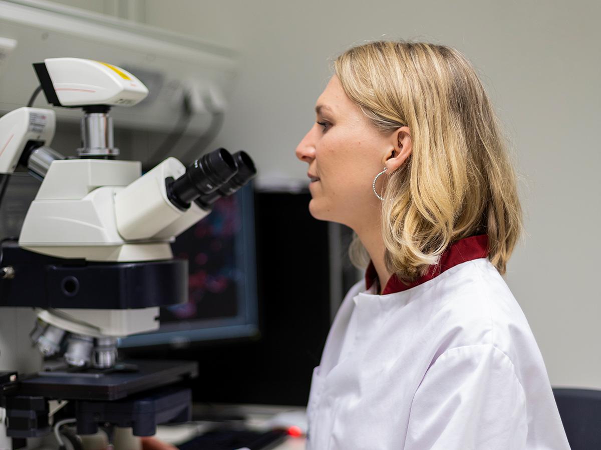 Portret van Amelie Bos achter de microscoop