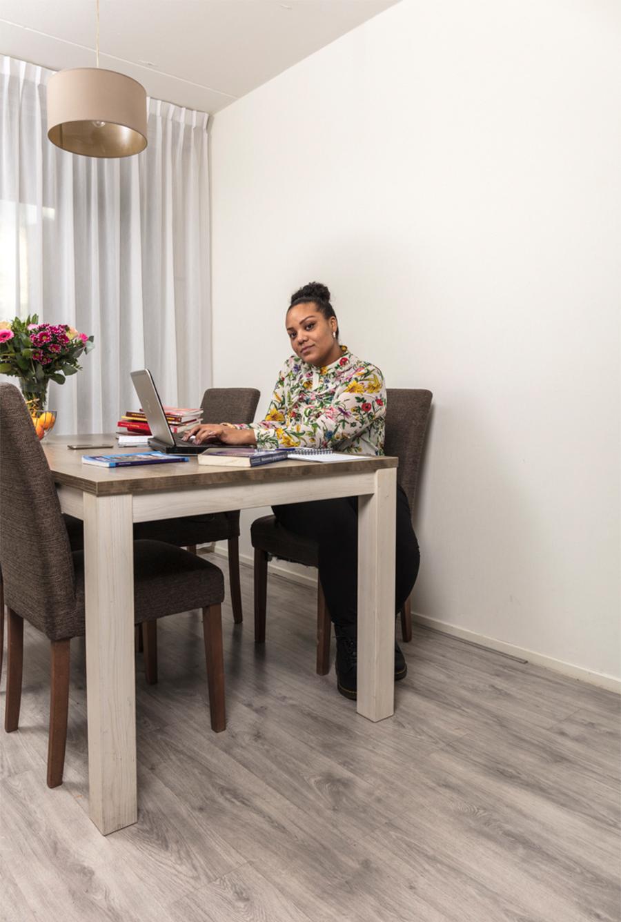 Omara achter haar laptop in de woonkamer. Ze hoopt eindelijk af te studeren