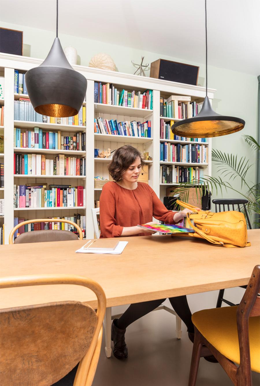 Mariska zit aan tafel en stopt haar studiespullen in haar tas. Op de achtergrond een grote boekenkast