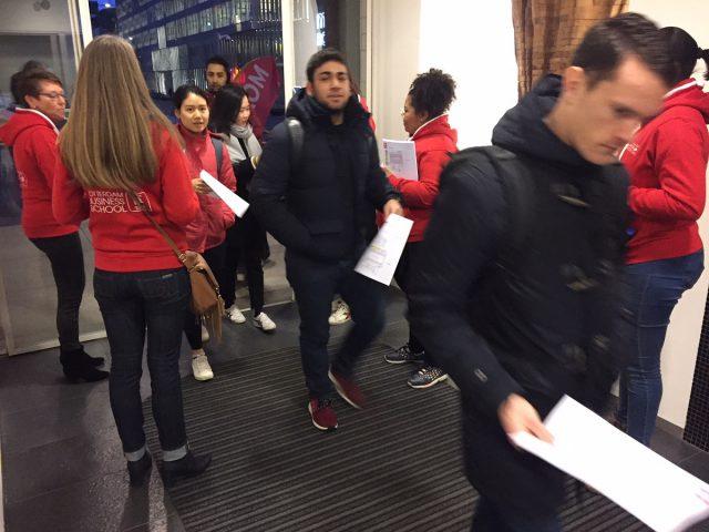 Dames in rode hoodies ontvangen de studenten