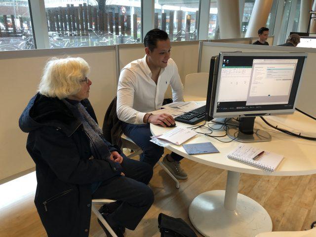 Accountancy-student Dias (r) helpt Riet van der Ham met haar belastingaangifte