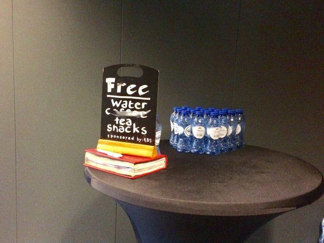 Op een tafeltje staan flesjes water en een bordje met de tekst: Free coffee, tea, water