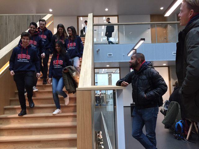 6 minor-studenten lopen van de trap op locatie Kralingse Zoom; allemaal dragen ze een blauwe RBS-trui, met de rode letters R, B en S erop
