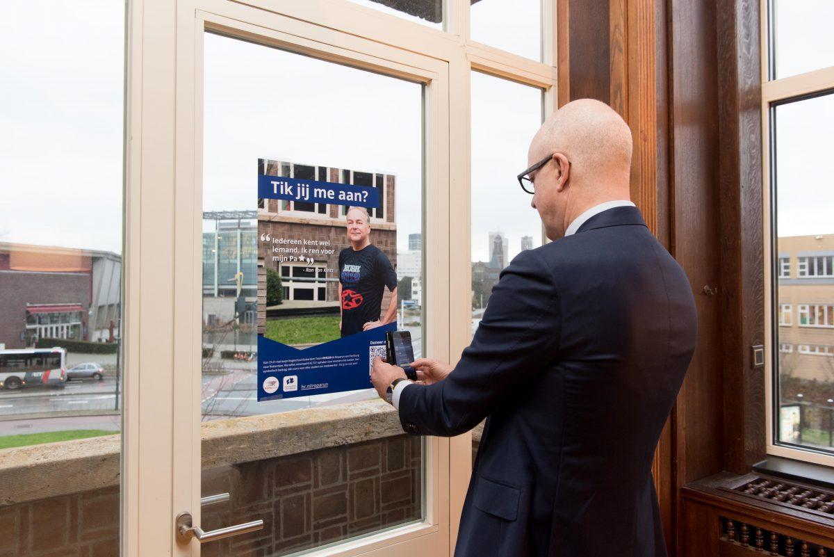 Collegevoorzitter Bormans doet de eerste donatie via de QR-code.