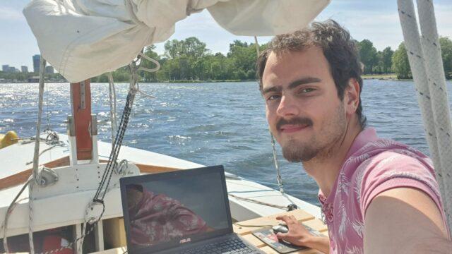 Yoeri achter z'n laptop op de Kralingse Plas