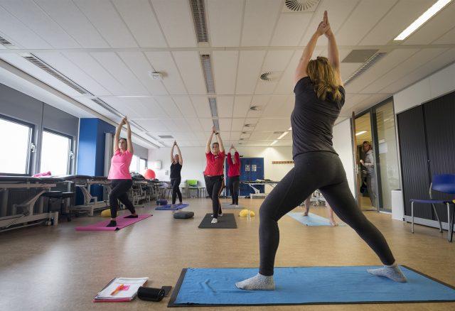 Foto van Wietske Willemse die met haar klas een high lunge yogapose aanneemt.