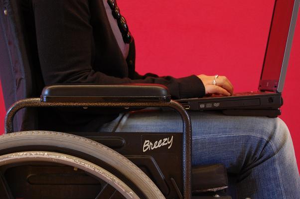 Student in een rolstiel met toetsenbord op het schoot