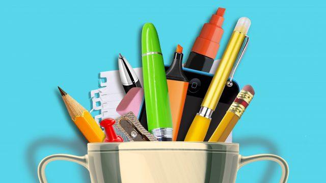 Bokaal met daarin pennen, potloden, papier en puntenslijpers.