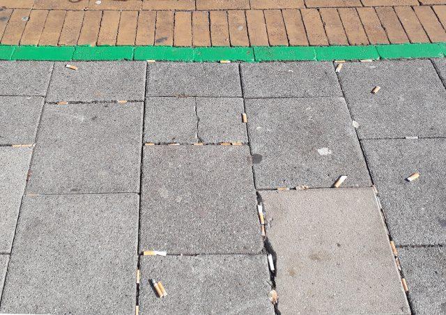 Foto van de groene lijn die de verboden te roken zone duidt.
