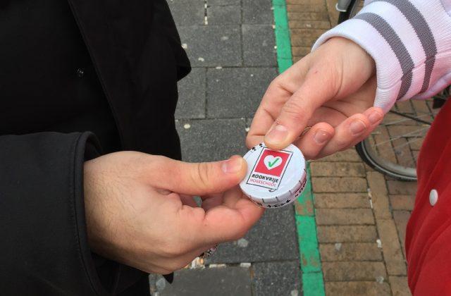 Studenten in rode HR-sweaters delen vandaag pepermuntjes uit aan rokers die op de juiste plek roken