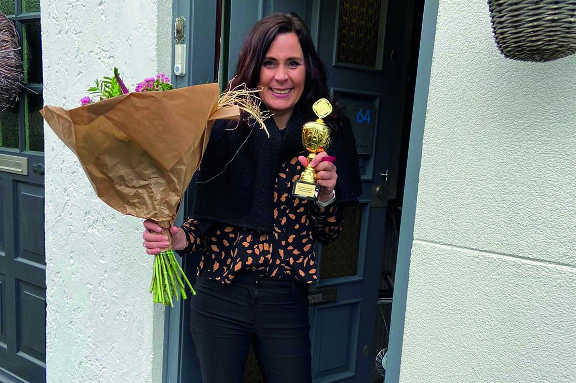 Miranda Sigmond op de stoep van haar huis met een bos bloemen