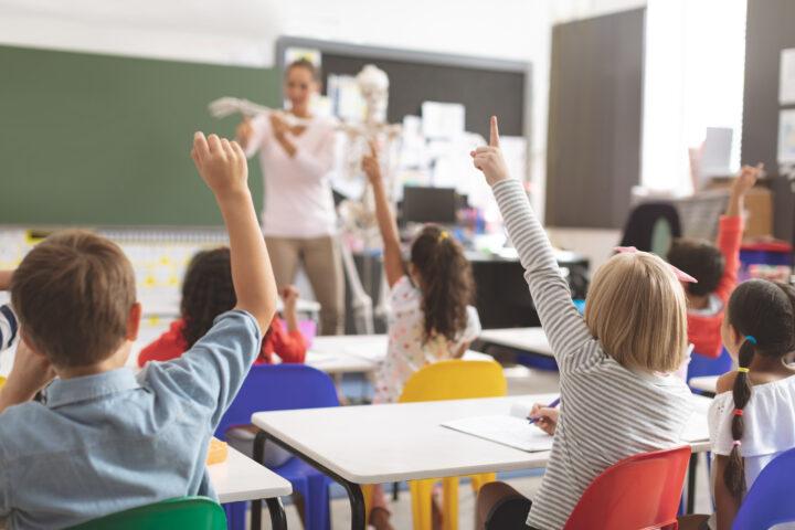klaslokaal basisschool, kinderen met vingers in de lucht